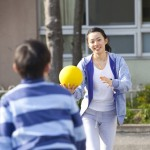 ドッヂボールをする小学生男子と女性教師