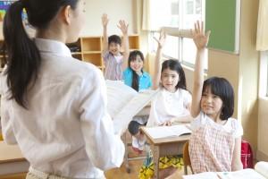 授業中挙手をする小学生