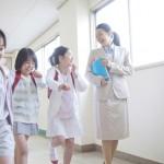廊下を歩く女性教師とはしゃぐ小学生女子