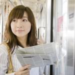 電車の中で新聞を読む女性