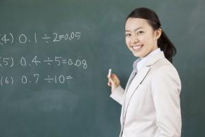 黒板に問題を書く女教師